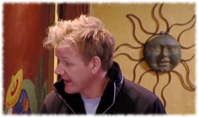 Chef Gordon Ramsay talking to Vic during Kitchen Nightmares with a sun wall hanging in the background on the restaurant wall.