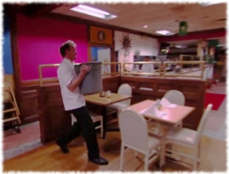 Chef Gordon Ramsay carries heavy garbage can type container of refried beans out to the dining room of Fiesta Sunrise.